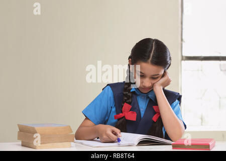 Rural girl sitting in classroom reading book - Stock Photo