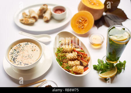 Still life from above on white tablecloth. Oriental dinner from soup with seeds, tempura shrimps and noodles with vegetables preparing for client. Three dishes lunch with mint tea ready for eating. - Stock Photo