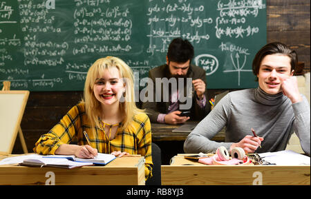 Modern teacher hipster writing on big blackboard with math formula. Be cool and you will be able to attract and retain lot more students - Stock Photo