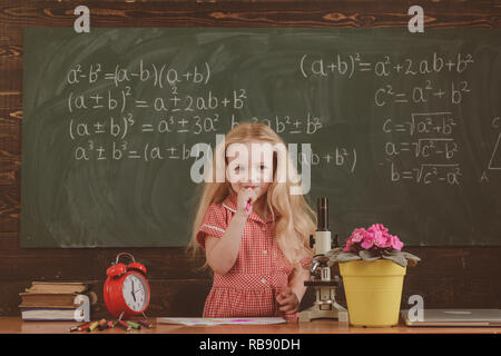 Little girl think of mathematical problem in classroom. Schoolchild solve problem in school - Stock Photo