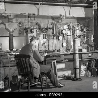 1950s, historical, male professor working in a science labarotary at Oxford University, England, UK doing experiments using a wide variety of equipment, including batteries, rubber tubes, gas canisters, pipes and pressure gauges. - Stock Photo