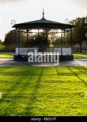 The Victorian bandstand in the Royal Pump Room gardens, Leamington Spa, England UK, with low sun behind casting long shadows. - Stock Photo