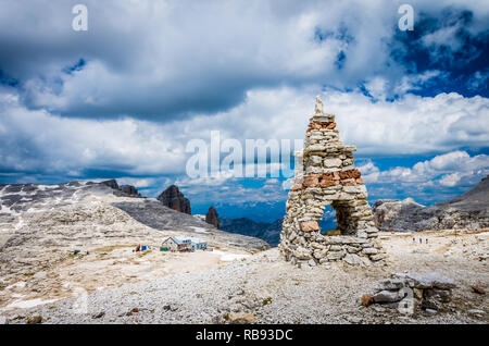 Sella massif, Dolomites mountains, Italian Alps. Cairn on the stone in the foreground and rifugio Boe in the second plane. Hiking to Piz Boe - Stock Photo