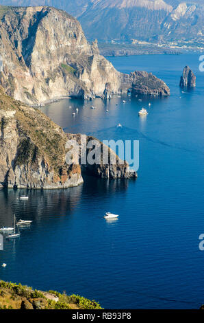 Stunning view of Valle Muria beach in Lipari and the Faraglioni. In the background the crater of Vulcano Island. Aeolian islands, Sicily - Stock Photo