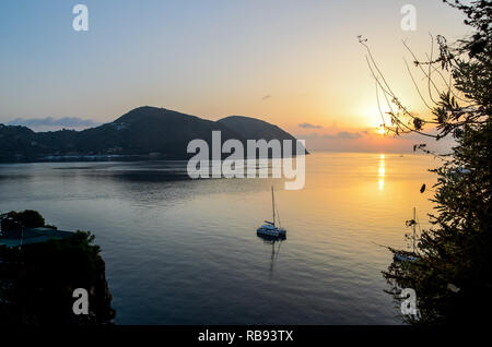 Stunning view of the sea, rocky coastline and boats in Lipari at sunset with faraglioni on the tyrrhenian sea. Aeolian islands, Sicily - Stock Photo