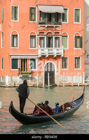 Venice, Italy - March 20, 2018: Venetian gondolier riding tourists on gondola at Grand Canal in Venice. - Stock Photo