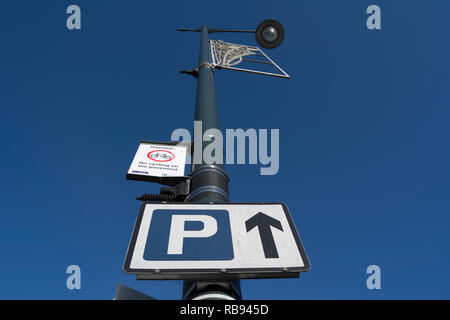 sign indicating car parking straight ahead and a sign warning not to cycle on the pavement, in whitton high street, middlesex, england - Stock Photo