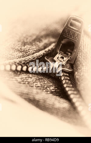 close up of a zip opening on some jeans in sepia - Stock Photo