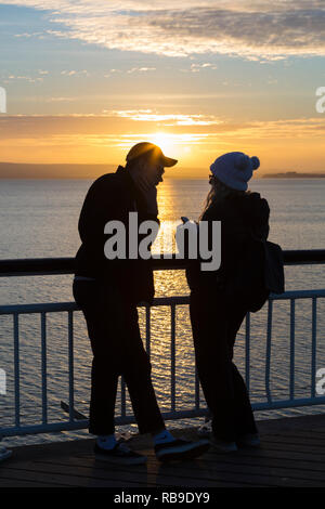 Bournemouth, Dorset, UK. 8th Jan, 2019. Beautiful sunset ends a lovely sunny day at Bournemouth beach. Couple on the pier. Credit: Carolyn Jenkins/Alamy Live News - Stock Photo