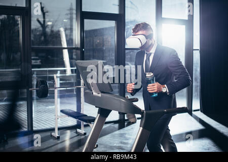 businessman in suit and virtual reality headset exercising on treadmill and holding sport bottle in gym - Stock Photo