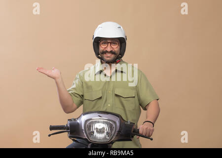 Smiling man wearing helmet sitting on a scooter and showing palm. - Stock Photo