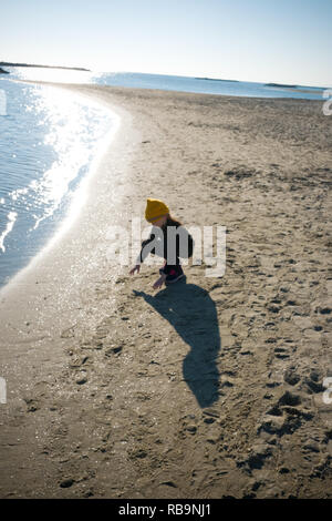 a six year old girl with woolly hat crouches to play with sand on a beach near the waters edge on a calm bright autumn day, Palavas les Flots, France - Stock Photo