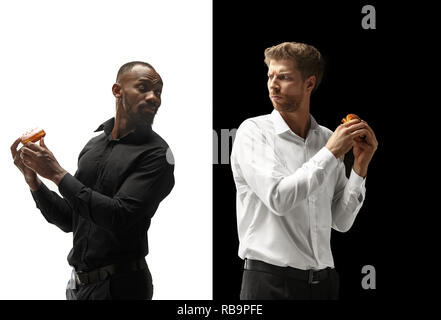 Men eating a hamburger and donut on a black and white background. The happy afro and caucasian men. The burger, fast, unhealthy food concept - Stock Photo