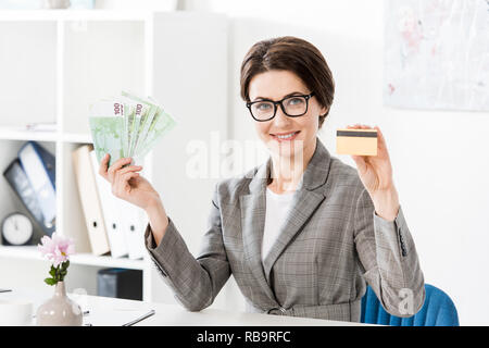 attractive businesswoman showing euro banknotes and credit card in office - Stock Photo