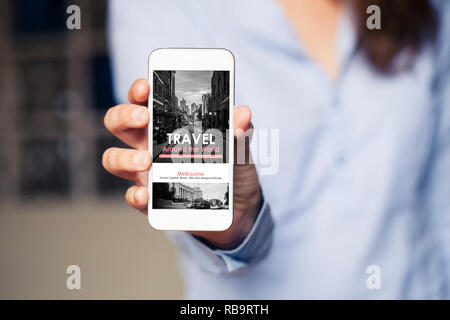 Travel agency website in a mobile phone screen while woman holds the device. - Stock Photo