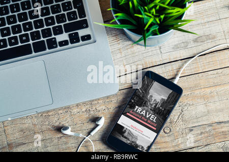 Mobile phone at the office with travel agency website in the screen, placed at the office. - Stock Photo