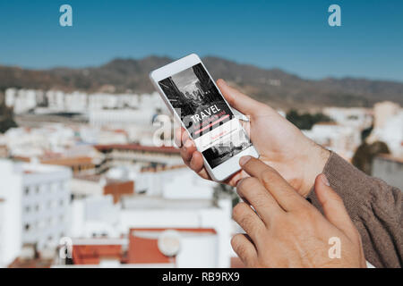 Man holding a mobile phone in the hand with travel agency website in the screen, touching it with the finger, with the city in the background. - Stock Photo