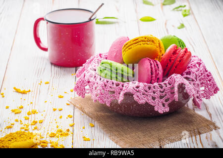 Assorted colorful sweet gentle soft French macaroons dessert cake macarons biscuit in bowl with knitted pink napkin on bright white table with red mug - Stock Photo