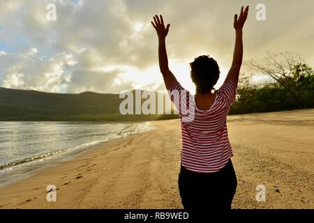 Woman holds arms up in freedom to celebrate sunrise on a beach, Smalleys Beach Camp Ground, Cape Hillsborough National Park, Qld, Australia - Stock Photo