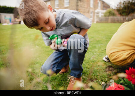 Young boy on an easter egg hunt with a friend. They are seaching for chocolate easter eggs in a back garden. - Stock Photo