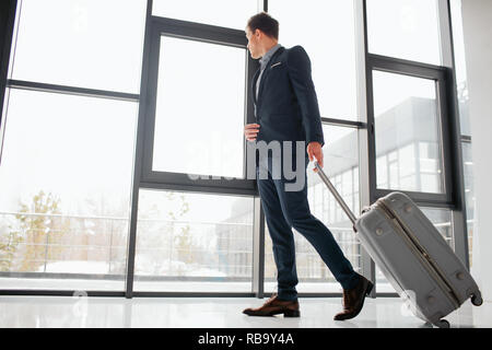 Young businessman in suit walks down hall in airport. He looks at window. Guy rolls suitcase. He looks confident - Stock Photo