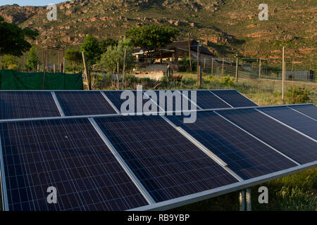 Living off the grid: solar panels provide electricity for the farm house in the background. - Stock Photo