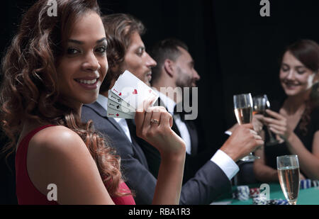 Woman at roulette table holding champagne glass in casino - Stock Photo
