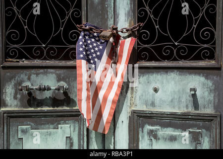 An American flag hangs on chained and padlocked door of a mausoleum. - Stock Photo