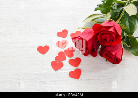 Valentines day red rose flower on white wooden background / Romantic love small red heart with fresh roses place on the table copy space - Stock Photo