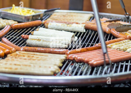different sausages in pita bread and without pita roast on a grill over the coals - Stock Photo