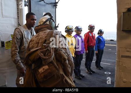 U.S. Marine Corps Gen. Robert B. Neller, 37th Commandant of the Marine Corps, prepares to depart from the flight deck of the amphibious assault ship USS Makin Island (LHD 8), in the Gulf of Aden, Dec. 23, 2016. Sailors involved in flight deck operations wear color-coded apparel that identifies their specialization. - Stock Photo