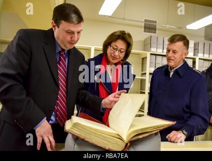 A National Archives member shows U.S. Coast Guard Commandant Adm. Paul Zukunft and his wife Fran DeNinno-Zukunft the original print of the Coast Guard Act of 1915, at the National Archives in Washington, D.C., Dec. 30, 2016. Passed by Congress and signed into law by President Woodrow Wilson, the Coast Guard Act of 1915 combined the Life-Saving Service and the Revenue Cutter Service into what is known today as the U.S. Coast Guard. - Stock Photo