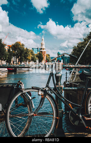 Close-up of Bike parked on a bridge in Amsterdam, Netherlands. Typical cityscape with Amstel river and motion clouds at the background - Stock Photo