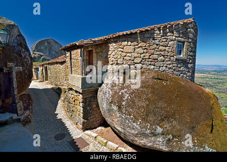 Narrow alley through granite stone houses and huge rocks in historic village Monsanto - Stock Photo