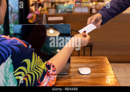 Businesswoman handing out business card to businessman in cafe. - Stock Photo