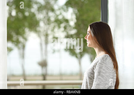 Happy woman looking outside through the window at home - Stock Photo