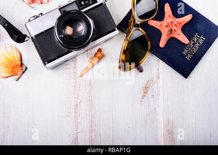 Vintage photo camera, passport, sunglasses and seashells border on wooden white background. Summer holiday design with copyspace. Traveling concept. - Stock Photo