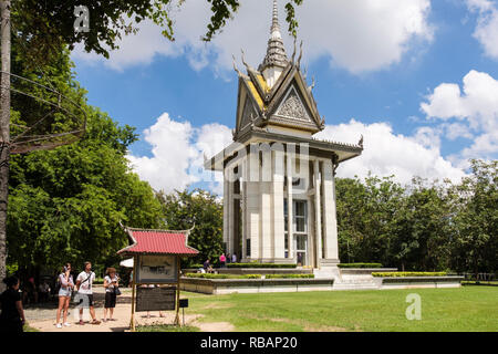 The Killing Fields Genocidal Centre memorial site with Buddhist Stupa containing human skulls and tourists reading sign Choeung Ek Phnom Penh Cambodia - Stock Photo