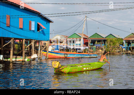 Houses on stilts and boats in floating village in Tonle Sap lake. Kampong Phluk, Siem Reap province, Cambodia, southeast Asia - Stock Photo