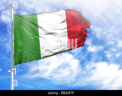 National flag of Italy on a flagpole in front of blue sky. - Stock Photo