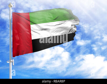 National flag of United Arab Emirates on a flagpole in front of blue sky. - Stock Photo