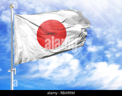 National flag of Japan on a flagpole in front of blue sky. - Stock Photo