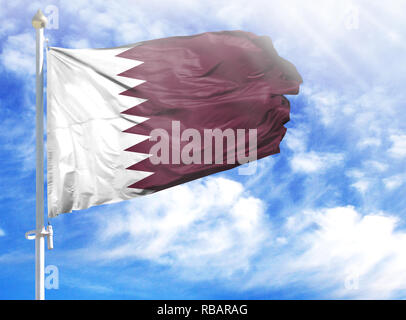 National flag of Qatar on a flagpole in front of blue sky. - Stock Photo
