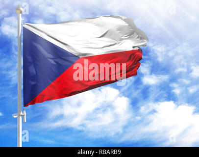 National flag of Czech Republic on a flagpole in front of blue sky. - Stock Photo
