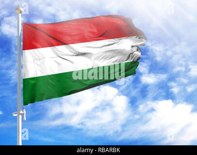 National flag of Hungary on a flagpole in front of blue sky. - Stock Photo