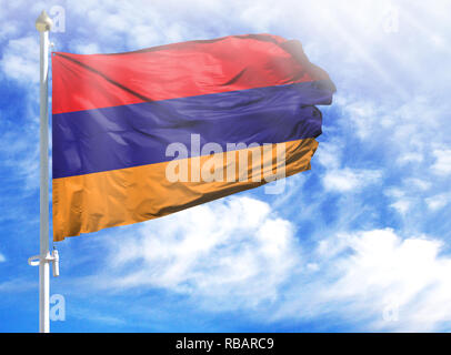 National flag of Armenia on a flagpole in front of blue sky. - Stock Photo