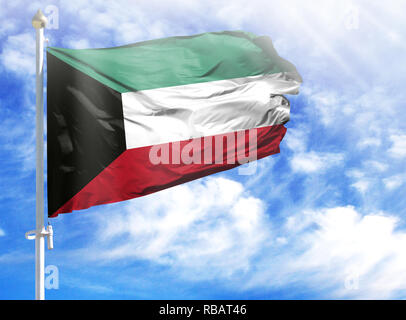 National flag of Kuwait on a flagpole in front of blue sky. - Stock Photo