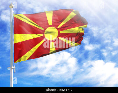 National flag of Macedonia on a flagpole in front of blue sky. - Stock Photo