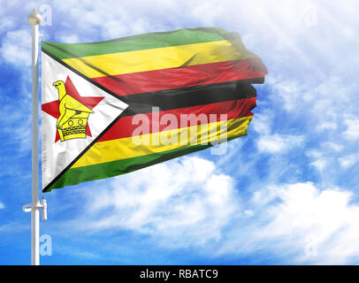 National flag of Zimbabwe on a flagpole in front of blue sky. - Stock Photo