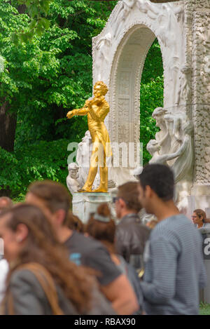 Vienna tourism, view of the golden Johann Strauss statue with a crowd of young tourists in the foreground, Stadtpark, Vienna, Wien, Austria. - Stock Photo